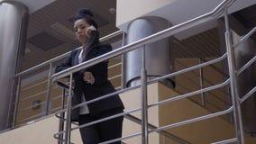 黑衣服的可爱的夫人在栏杆在电话倾斜并且谈话 股票视频
