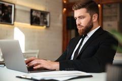 黑衣服的年轻严肃的有胡子的商人使用膝上型计算机 免版税库存照片