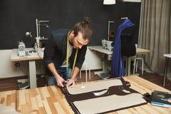 黑衣服的成熟创造性的英俊的深色头发的白种人男性时装设计师删去衣裳的从织品分开 库存图片