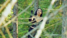 黑衣裳的一个快活的年轻巫婆在舞蹈转动在森林万圣夜里 哥特式样式 股票视频