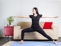 黑衣裳的美丽的白种人深色的妇女在蓝色瑜伽 免版税库存照片