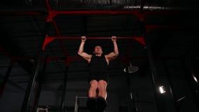 黑衣裳的运动员在健身房执行在单杠的一个电源输出口 一个广角看法从下面 影视素材