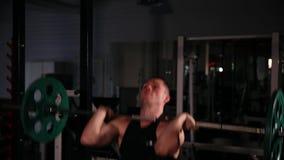 黑衣裳的运动员推挤与重量的酒吧在他的头上在动态节奏 来到旋转门 股票录像