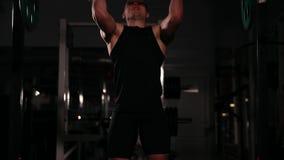 黑衣裳的运动员推挤与重量的酒吧在他的头上在动态节奏 股票视频
