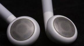 黑表面上的耳机 免版税库存图片