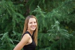黑衬衣的令人惊讶的微笑的妇女有站立近的云杉的树的长的亮光头发的在夏时 免版税库存照片