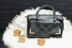 黑袋子和礼物盒在白色毛皮 时兴的概念 holida 免版税图库摄影