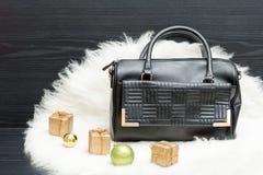 黑袋子和礼物盒在白色毛皮 时兴的概念 holida 库存图片