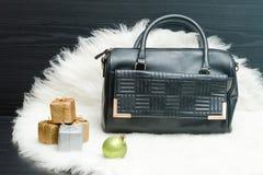黑袋子和礼物盒在白色毛皮 时兴的概念 holida 免版税库存照片