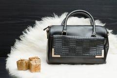 黑袋子和礼物盒在白色毛皮 时兴的概念 holida 免版税库存图片