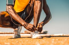 黑赛跑者领带他的在海滩的鞋子 免版税库存照片