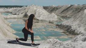 黑运动服的运动的深色的女孩训练反对与大海的一件白色白垩沙子猎物 在每条腿的刺 股票录像