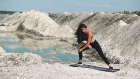 黑运动服的运动的深色的女孩训练反对与大海的一件白色白垩沙子猎物 执行滚动从 股票录像