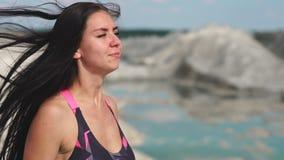 黑运动服的运动的深色的女孩训练反对与大海的一件白色白垩沙子猎物 执行burpee 股票视频