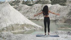 黑运动服的运动的深色的女孩训练反对与大海的一件白色白垩沙子猎物 执行burpee 股票录像