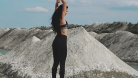 黑运动服的运动的深色的女孩训练反对与大海的一件白色白垩沙子猎物 有黑发的女孩 股票录像