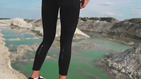 黑运动服的运动的深色的女孩训练反对与大海的一件白色白垩沙子猎物 脚特写镜头  股票视频