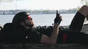 黑运动服的骑自行车者在有反射在他的太阳镜的太阳的长凳藏品手机 有盔甲的骑自行车者在使用他的 影视素材