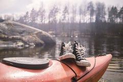 黑运动鞋在春天太阳ag的光芒的一艘皮船站立 库存照片