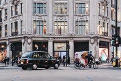黑通过在耐克镇,伦敦,英国前面的小室和人力车 免版税库存照片