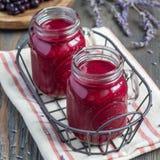 黑醋栗,希腊酸奶、蜂蜜和淡紫色圆滑的人在玻璃瓶子,方形的格式 免版税库存照片