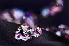 黑金刚石在紫色丝绸小的堆珠宝 库存图片