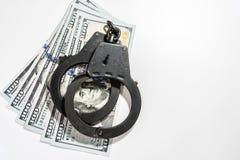 黑金属手铐在100美金说谎 免版税库存照片