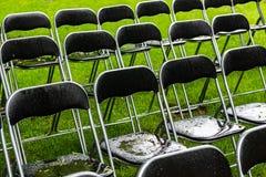 黑金属椅子在雨中站立外部在公园 空的观众席,绿草,waterdrops,特写镜头 库存照片