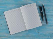 黑钢笔和铅笔有一个开放笔记本的在蓝色木桌上 顶视图 图库摄影