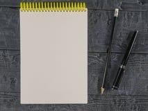 黑钢笔和铅笔有一个开放笔记本的在黑木桌上 顶视图 库存图片
