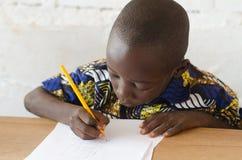 黑非洲男孩在采取笔记的学校在类期间 库存图片