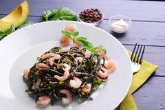 黑面团用虾和鲕梨在板材调味 免版税库存图片