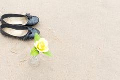黑鞋子和黄色玫瑰开花到在backgr的瓶 库存图片