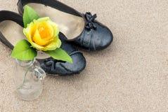 黑鞋子和黄色玫瑰开花到在backgr的瓶 免版税库存照片