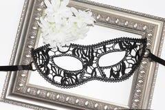 黑鞋带眼罩、葡萄酒框架和白花 库存照片