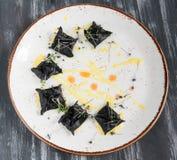 黑馄饨用海鲜 在板材顶视图 在木黑背景 免版税库存照片