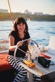 黑驾驶豪华游艇的衬衣和镶边的裙子的年轻俏丽的微笑的妇女在海,日落 免版税图库摄影
