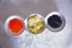 黑鱼子酱,红色鱼子酱,在碗的黄油 库存照片