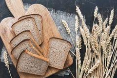 黑麦切的黑麦面包和钉在黑暗的背景的 平的位置 库存图片
