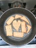 黑麦面包在油,油煎方型小面包片,以心脏的形式suhariki的一个煎锅油煎 免版税库存图片