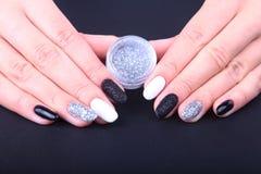 黑,白色钉子艺术修指甲 与闪闪发光的假日样式明亮的修指甲 瓶指甲油 秀丽手 免版税库存图片