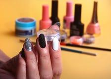 黑,白色钉子艺术修指甲 与闪闪发光的假日样式明亮的修指甲 秀丽手 时髦的钉子,指甲油 免版税图库摄影