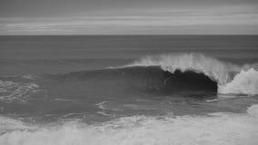黑&白色碰撞在一多云天的海洋和波浪 库存照片