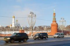 黑SUV和两辆小巴沿在Kremli背景的高速公路迅速移动  免版税库存图片