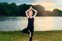 黑T恤杉和绑腿的少女坐在莲花姿势的一块石头在湖附近 库存照片