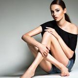黑T恤杉和蓝色短裤的美丽的妇女 免版税图库摄影