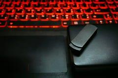 黑usb一刹那推进记忆棍子的关闭和在膝上型计算机的便携式的可移动的外在硬盘存贮有美丽的红色backli的 库存图片