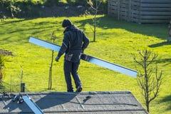 默尔斯,德国- 2018年2月05日:平衡在有金属面对的屋顶的盖屋顶的人 图库摄影
