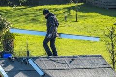 默尔斯,德国- 2018年2月05日:平衡在有金属面对的屋顶的盖屋顶的人 库存照片