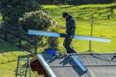 默尔斯,德国- 2018年2月05日:平衡在有金属面对的屋顶的盖屋顶的人 免版税库存照片